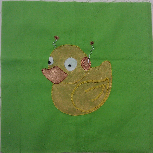 Robotic rubber-duck made of gold and bronze fabric paint, bronze, silver, and yellow embroidery thread, and two black/white beads for pupils, on a bright green background