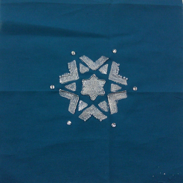 A snowflake made of silver fabric paint, couched silver embroidery thread, and some white and crystal beads, on dark blue background